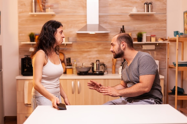 Disappointed wife looking at husband after she finds he is cheating with another woman. heated angry frustrated offended irritated accusing her man of infidelity showing him messages.