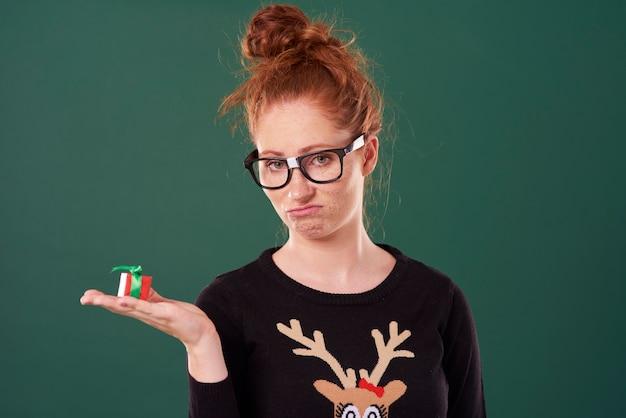 クリスマスプレゼントを持っている失望した女性