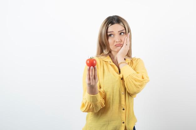 白い壁に赤いトマトを持っている失望した女性。