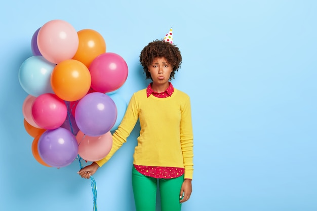 Disappointed woman holds multicolored balloons while posing in a yellow sweater