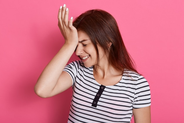La donna delusa tiene il palmo della mano sulla fronte, si rammarica di aver fatto qualcosa di sbagliato, vestita di maglietta a righe, posa sul muro rosa, si dimentica di un compito importante.
