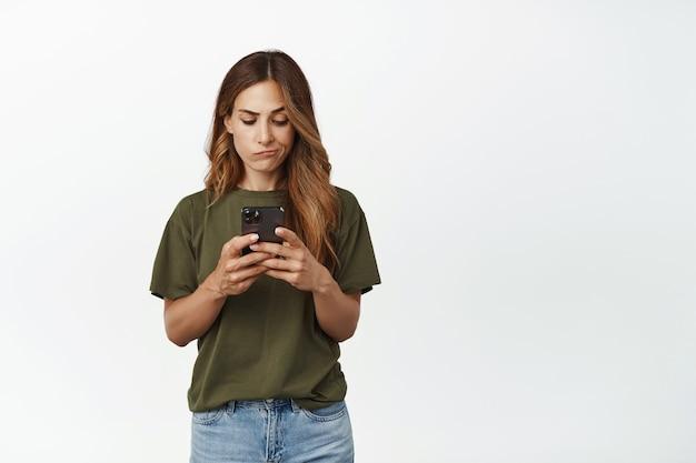 Разочарованная женщина смотрит на мобильный телефон с расстроенным хмурым лицом, не хватает денег на банковском счете в приложении для смартфона