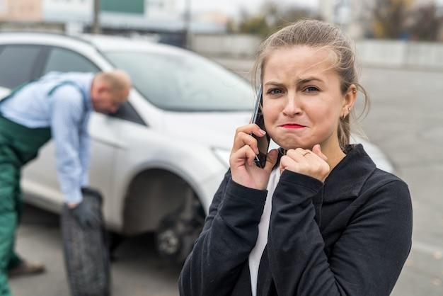 전화를 호출하는 자동차 서비스에 실망 된 여자