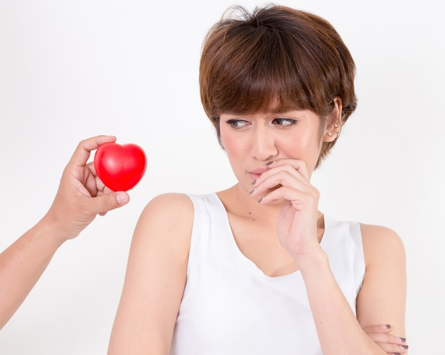 Disappointed woman rejecting the red heart of her boyfriend. isolated on white background. studio lighting.