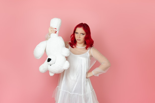 Disappointed woman in a white dress  holds a large white teddy bear upside down by the paw