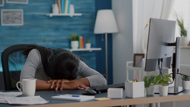 Disappointed workaholic student sleeeping on desk table in living room after working remote from home at job project deadline