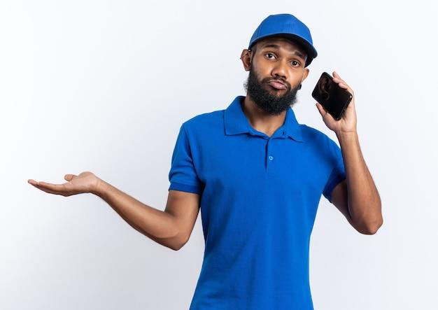 Giovane uomo di consegna afroamericano deluso che parla al telefono isolato su fondo bianco con lo spazio della copia