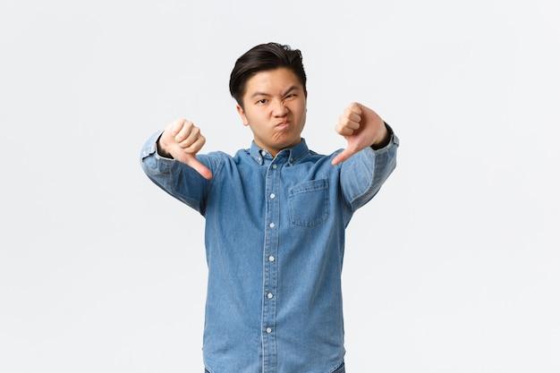 悪い品質に不平を言っている失望した若いアジア人男性は、親指を下に向けて顔をゆがめ、不機嫌になり、面白がらず、嫌いで反対し、白い背景に立っていました。