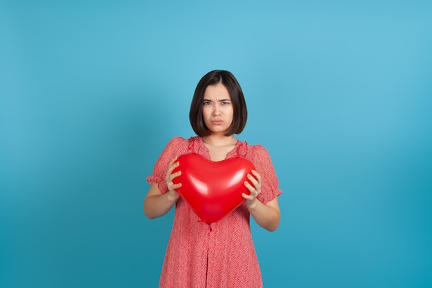 Disappointed young asian woman holding a red heart shaped balloon on valentine's day