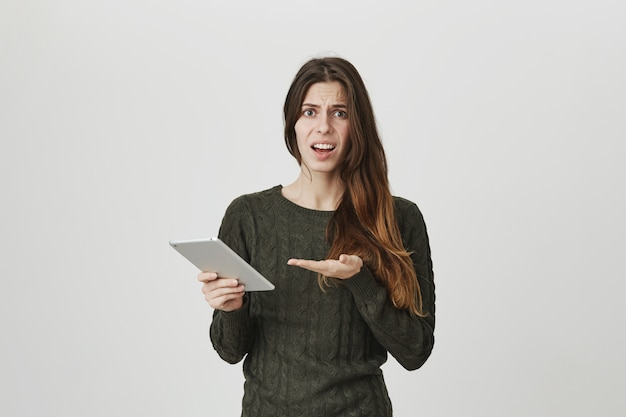 Disappointed young attractive woman complaining about something in digital tablet