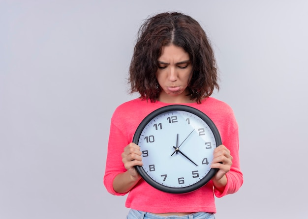 Disappointed young beautiful woman holding clock and looking at it on isolated white wall with copy space