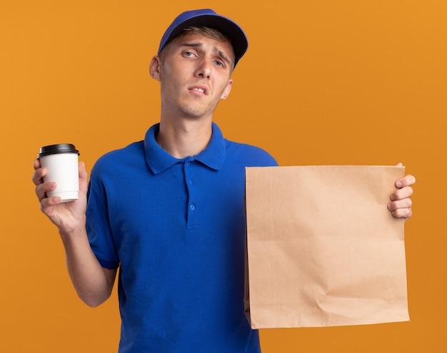 Разочарованный молодой блондин посыльный держит бумажный пакет и чашку, изолированные на оранжевой стене с копией пространства