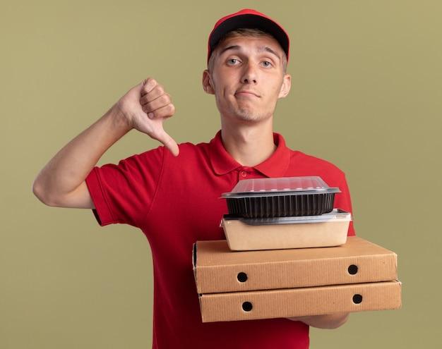 Deluso giovane ragazzo delle consegne biondo pollice in giù e tiene i pacchetti di cibo su scatole per pizza isolate su parete verde oliva con spazio di copia