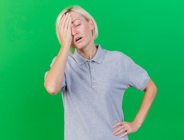 失望した若いブロンドの病気のスラブ女性は顔に手を置きます