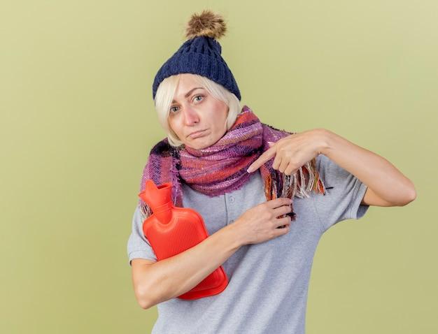 冬の帽子とスカーフを身に着けている失望した若い金髪の病気のスラブ女性は、コピースペースのあるオリーブグリーンの壁に隔離された湯たんぽを保持し、指さします