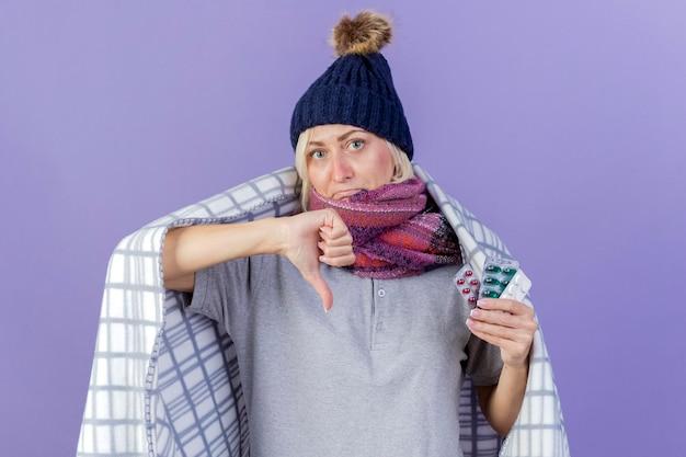 겨울 모자를 쓰고 실망 된 젊은 금발의 아픈 슬라브 여자
