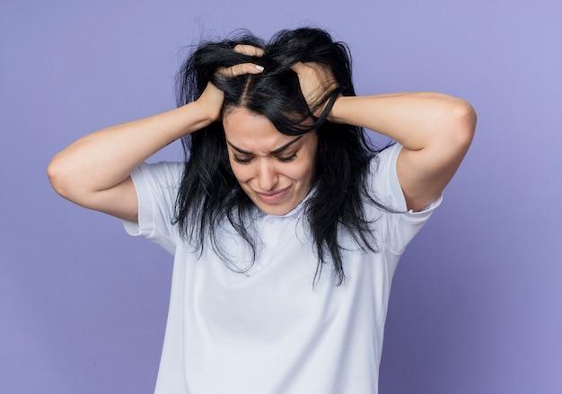 La giovane ragazza caucasica castana delusa tiene la testa e guarda in basso isolato sulla parete viola