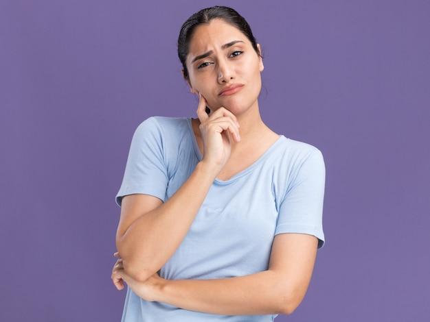 Una giovane ragazza caucasica bruna delusa mette la mano sul mento e guarda la telecamera isolata sul muro viola con spazio per le copie