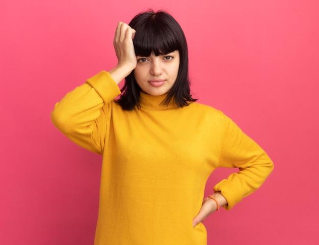 La giovane ragazza caucasica castana delusa mette la mano sulla testa isolata sulla parete rosa con lo spazio della copia