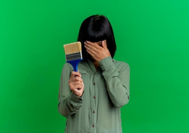 Разочарованная молодая брюнетка кавказская женщина кладет руку на лицо, держа кисть, изолированную на зеленом фоне с копией пространства