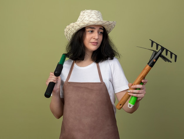 Disappointed young brunette female gardener in uniform wearing gardening hat holds and looks at gardening tools isolated on olive green wall