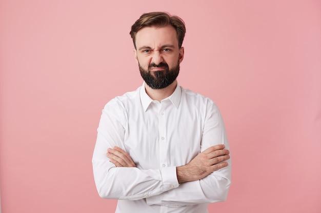 Разочарованный молодой брюнет с пышной бородой и короткой стрижкой, нахмуренный и надутый, стоит у розовой стены, скрестив руки, одетый в строгую одежду