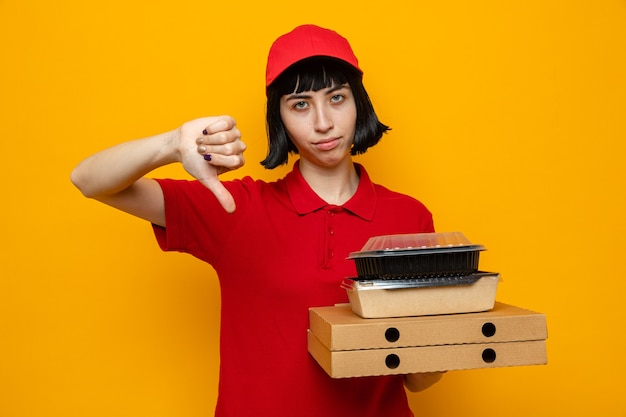 Giovane ragazza caucasica delusa che tiene in mano contenitori per alimenti con imballaggi su scatole per pizza