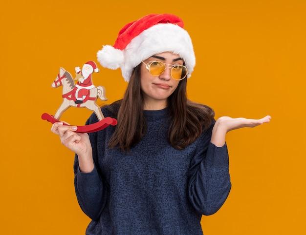 サンタの帽子とサングラスで失望した若い白人の女の子は、ロッキングホースの装飾にサンタを保持し、コピースペースでオレンジ色の背景に隔離された手を開いたままにします