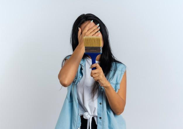 Разочарованная молодая кавказская девушка кладет руку на лицо и держит кисть для рисования