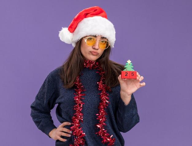Delusa giovane ragazza caucasica in occhiali da sole con cappello da babbo natale e ghirlanda intorno al collo tiene l'ornamento dell'albero di natale isolato sulla parete viola con spazio di copia