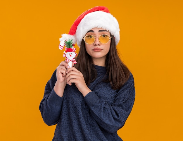 Disappointed young caucasian girl in sun glasses with santa hat holds candy cane isolated on orange wall with copy space