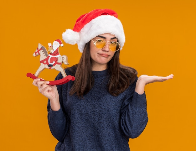 Disappointed young caucasian girl in sun glasses with santa hat holds santa on rocking horse decoration and keeps hand open isolated on orange background with copy space