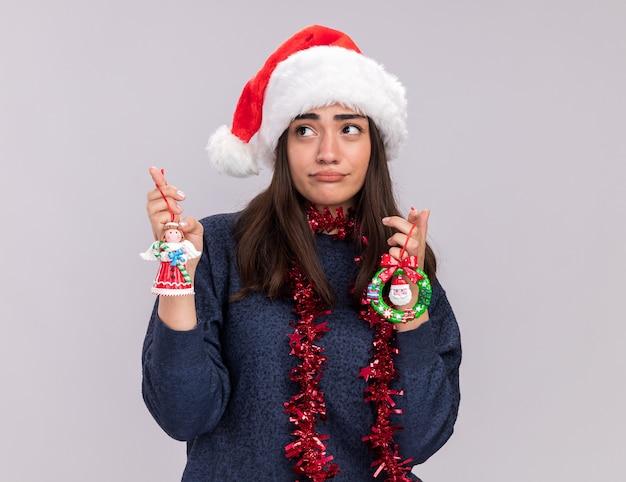 La giovane ragazza caucasica delusa con il cappello della santa e la ghirlanda intorno al collo tiene i giocattoli dell'albero di natale che esaminano il lato