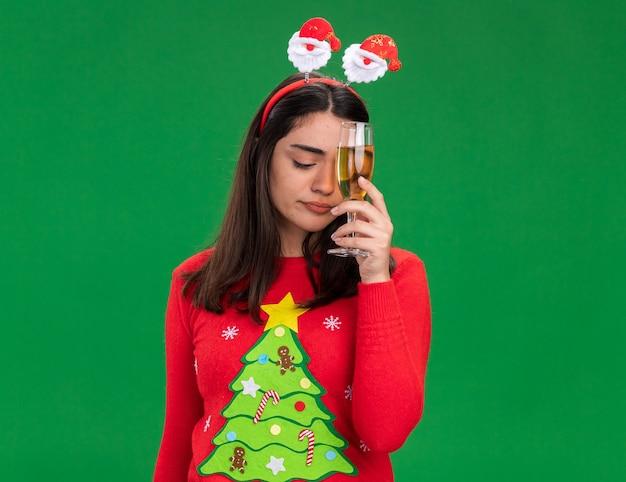 산타 머리띠와 실망 된 젊은 백인 여자 보유 복사본 공간이 녹색 배경에 고립 된 샴페인 잔