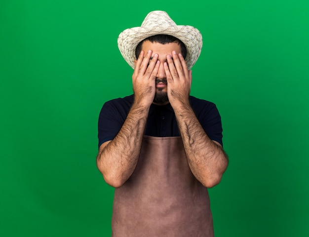 Disappointed young caucasian male gardener wearing gardening hat covering eyes with hands isolated on green wall with copy space