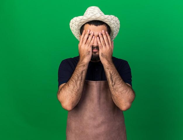 Разочарованный молодой кавказский садовник в садовой шляпе, закрывающий глаза руками, изолированными на зеленой стене с копией пространства