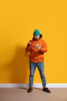 실망한. 스마트 폰, serfing, 채팅, 도박을 사용하는 젊은 백인 남자. 노란색 벽에 고립 된 전체 길이 초상화. 현대 기술, 밀레 니얼 세대, 소셜 미디어의 개념.