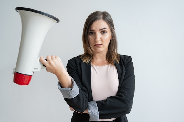 Disappointed young caucasian woman holding megaphone