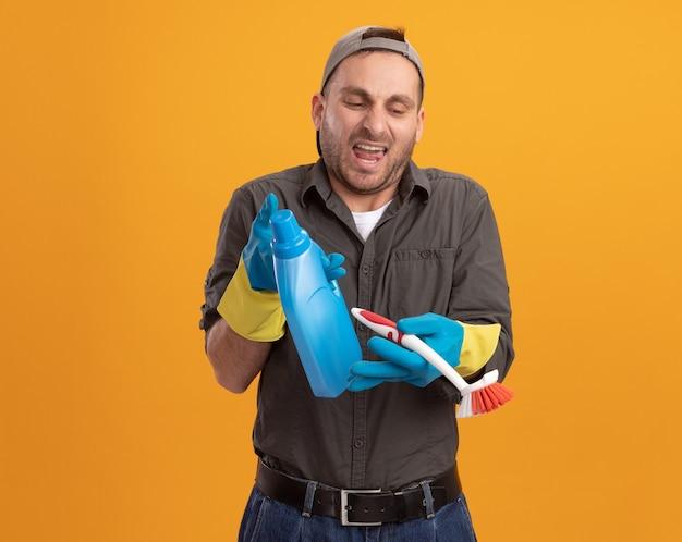 Giovane uomo delle pulizie deluso che indossa abiti casual e berretto in guanti di gomma che tengono la spazzola e la bottiglia di pulizia con i prodotti per la pulizia che urlano in piedi sopra la parete arancione