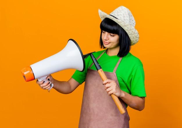 ガーデニング帽子をかぶった制服を着た失望した若い女性の庭師は熊手を保持し、スピーカーを見て