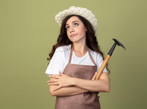 Разочарованная молодая женщина-садовник в униформе в садовой шляпе стоит со скрещенными руками и граблями, изолированными на оливково-зеленой стене