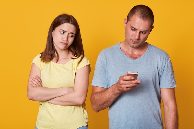 실망 어린 소녀 혼자, 자신의 장치에 초점을 맞춘 접힌 팔로 서 그녀의 남자 친구를보고 피곤