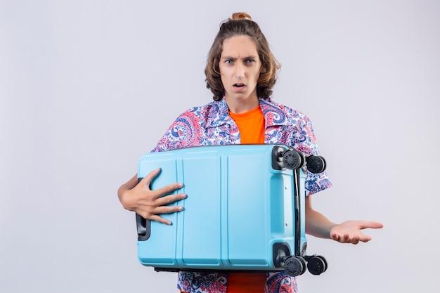 旅行スーツケースを持って失望した若いハンサムな男を見て驚いた立って