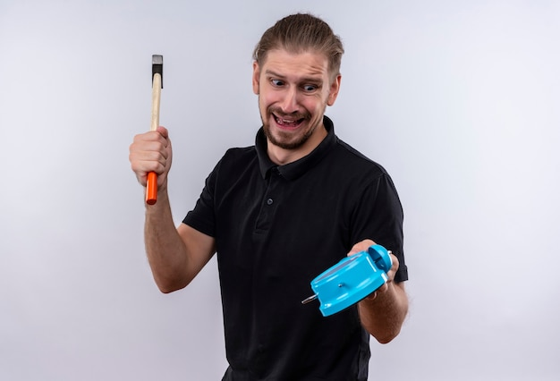 Disappointed young handsome man in black polo shirt holding alarm clock and swinging a hammer going to break the clock standing over white background