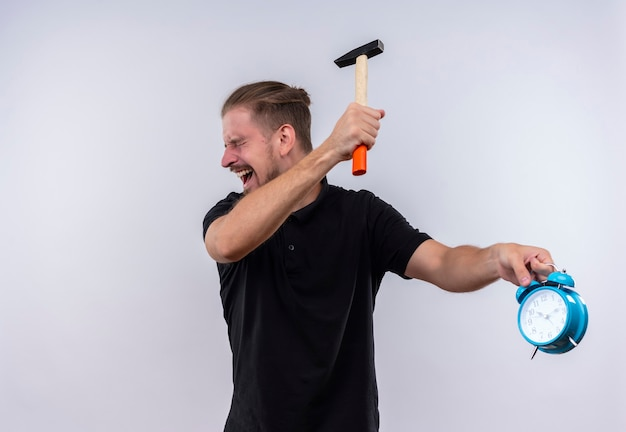 Disappointed young handsome man in black polo shirt with a hammer going to break alarm clock in his hand with aggressive expression on face standing over white background