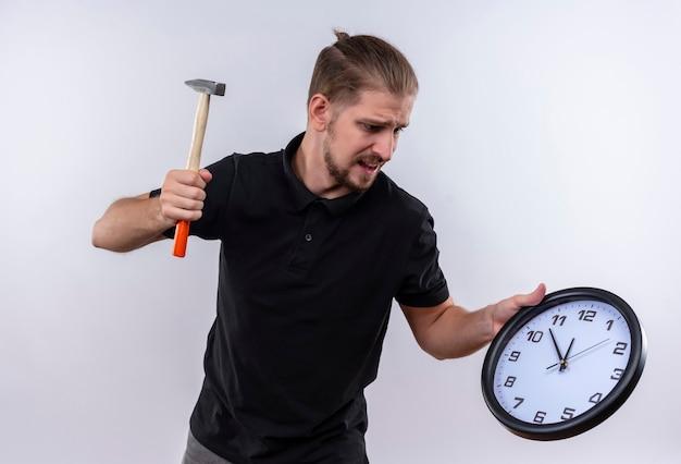 壁掛け時計を押しながら白い背景の上に立っている時計を壊すつもりのハンマーを振る黒いポロシャツで失望した若いハンサムな男