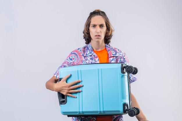 顔をしかめ顔立ちでカメラ目線のスーツケースを持って失望した若いハンサムな旅行者男