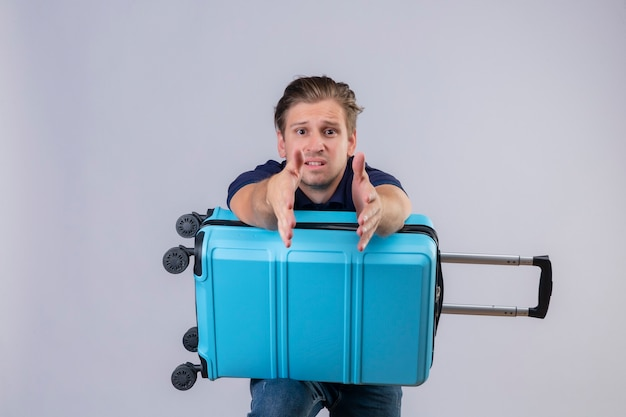 Disappointed young handsome traveler guy standing with suitcase stretching hands out  asking for help