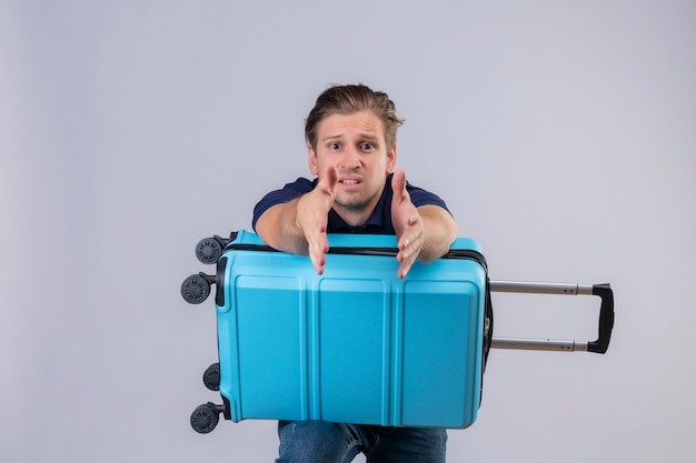 Disappointed young handsome traveler guy standing with suitcase stretching hands out looking at camera asking for help over white background