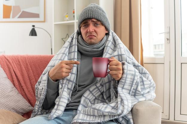 Deluso giovane uomo malato con sciarpa intorno al collo indossando cappello invernale avvolto in plaid tenendo e puntando alla tazza seduto sul divano in soggiorno
